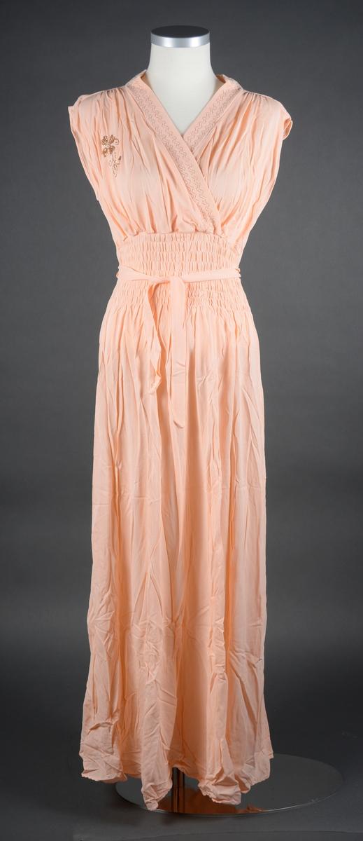 """En nattkjole laget av lys ferskenfarget nylonstoff. Kjolen har sidesømmer og en søm midt bak. Over byste har kjolen V-utringning med omslag (høyre side går delvis over venstre side). Kanten på utringningen går over til krage som igjen går over til kant på utringning. Kanten har dekor i form av sikksakk-søm med gulltråd (to doble sømmer). På høyre bryst er det sydd en blomst med stilk og blader i gulltråd. Bysten er sydd slik at den er rynket mot skuldrene og mot livet. I livet er det vaffelsøm (13cm bredt felt) slik at livet er smalt men elastisk. I livet er det sydd på et bånd/belte i hver side som kan knytes bak. Kjolen er ermeløs. Nattkjolen er i størrelse 44. Kjolen ligger i en eske, trolig originalemballasjen. Esken er laget av papp. Lokket til esken er i fargene blå, svart og hvitt. Motivet er en måne, stjernehimmel, en flyvende fugl og en kjole. På lokket er det et klistremerke oppå og et på kortsiden med produktinformasjon. Noe er trykt på og noe er skrevet med penn. På undersiden av esken er det klistret på et rosa og svart klistremerke fra P. Christensens trikotasjefabrikk. Det er også skrevet tall på undersiden, trolig prisen. For mer informasjon se """"Påført tekst/merker""""."""