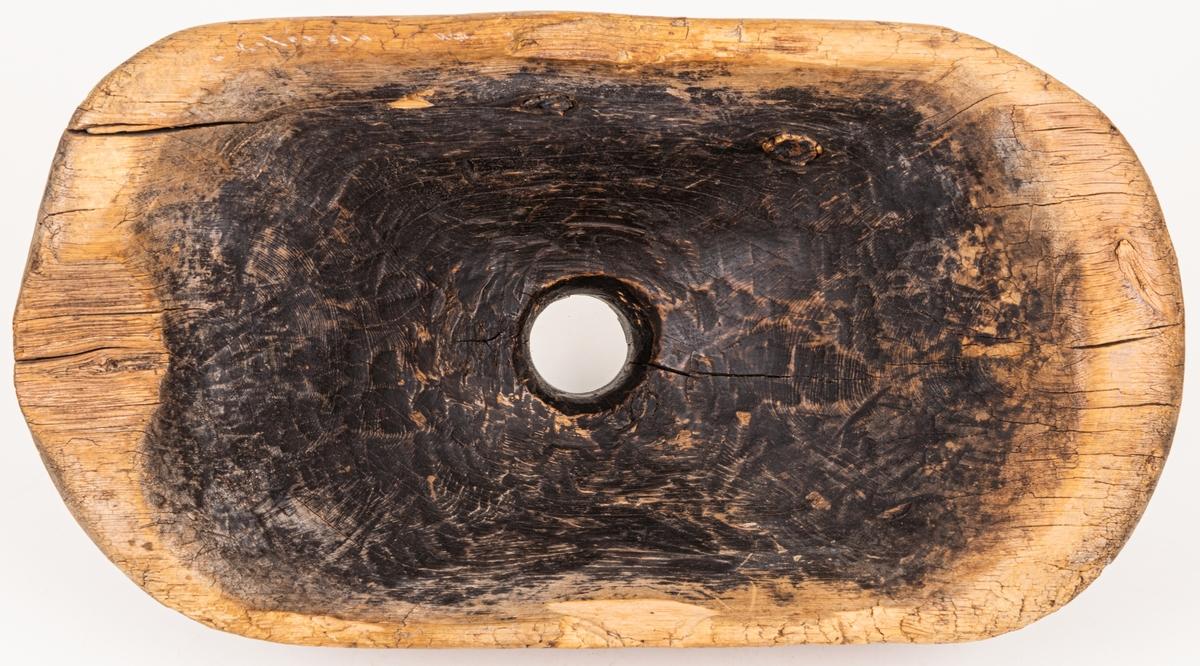 Tunntratt av trä, avlång med kort naturvuxen hals. Svart beläggning på hela insidan. I övrigt omålad. Längt 41 cm, bredd 22 cm. Höjd 19 cm. Undersidan ristad: S.SS 1745.