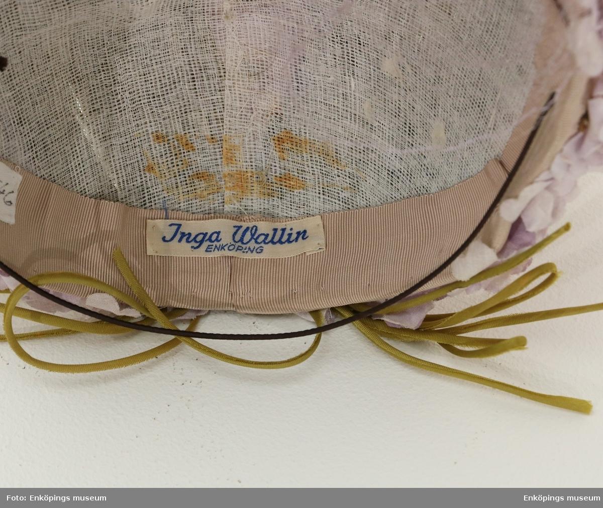 Styv gasväv klädd med ljusgröna band, syrenlila tygblommor och flor. Tillverkad av Inga Wallin, Enköping, Sverige. ( Förvaras i hattask EM7549).