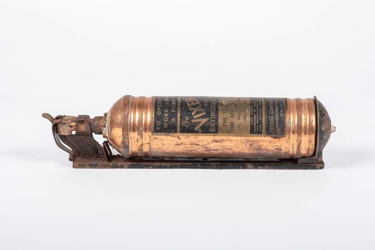 Sylinderformet brannslokningsapparatet med pumpe på toppen, som sitter i et stativ til å henge på veggen.