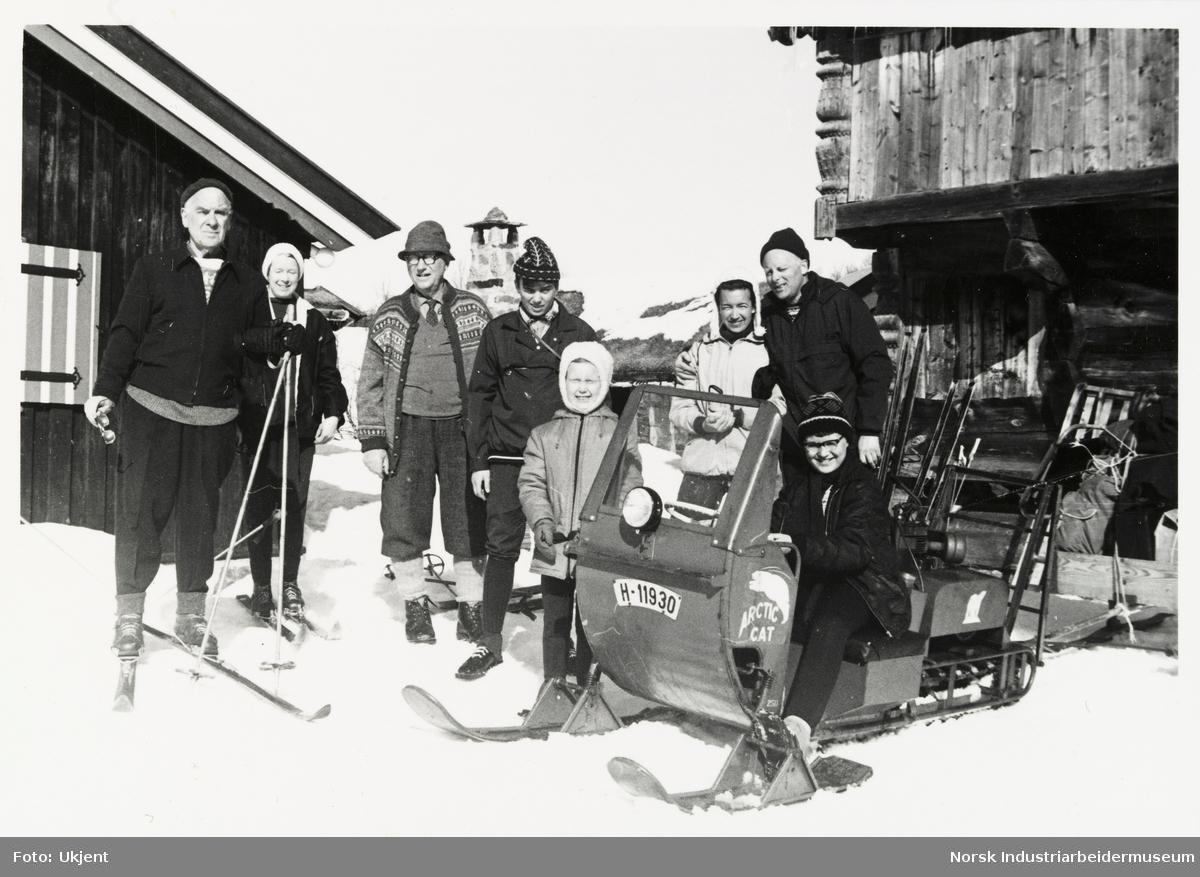 Mennesker står på hyttetun i snøen ved loft på Sundet. Menneskene har turantrekk, noen har ski på bena og en person sitter på snøskuter.