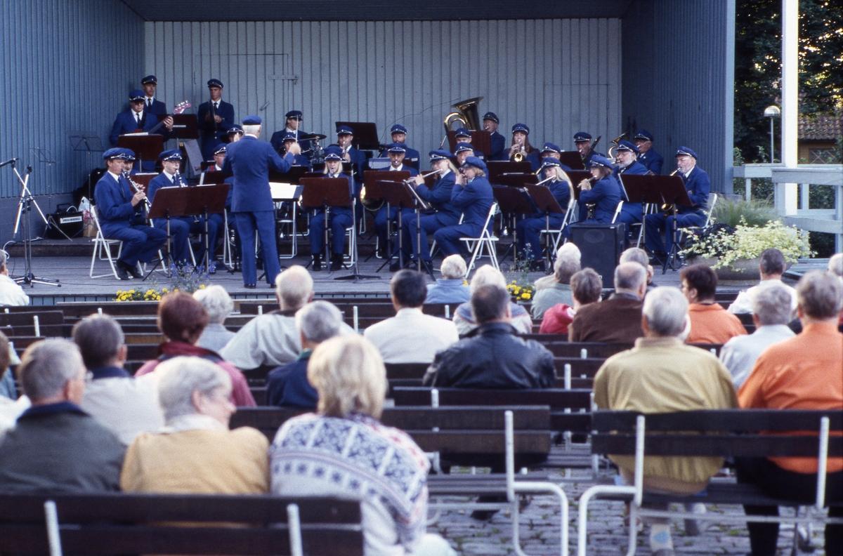 En blåsorkester uppträder, för publiken, i Olof Ahllöfs park.