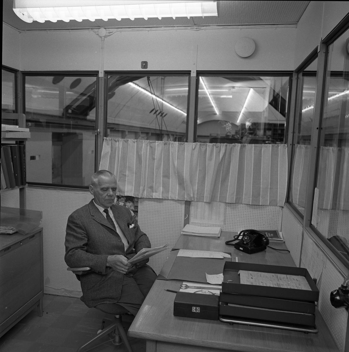 Alf Hedlund, maskinmästare på Centrala Verkstaden Arboga. Han sitter på sitt kontor där han har skrivbord, telefon och bokhylla.