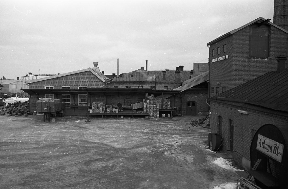 Arboga Bryggeris lastkaj med öl packade i lådor. En man arbetar med lådorna. En vagn är lastad. Snö efter husväggen. 1950-talet.  Anläggningen var färdigbyggd 1899 och verksamheten startade 1 november samma år. 24 oktober 1980 tappades det sista ölet, på bryggeriet. Märket var Dart. Läs om Arboga Bryggeri i hembygdsföreningen Arboga Minnes årsbok 1981