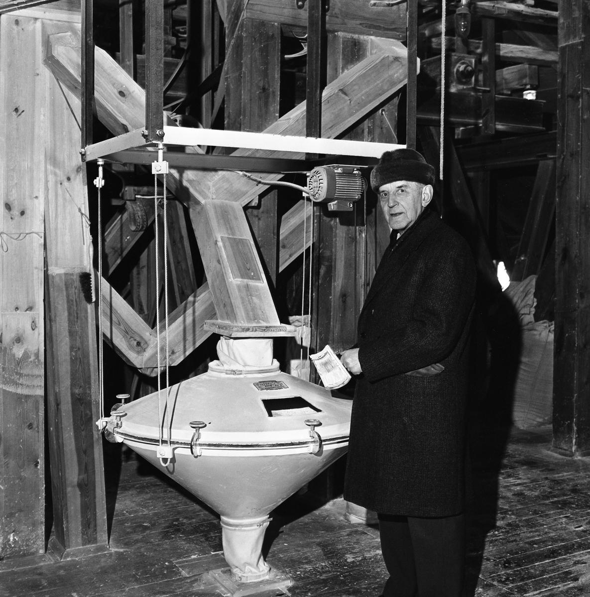 Arboga Kvarn och Maltfabrik, interiör. En äldre man iklädd ytterrock och pälsmössa. Fyllda säckar skymtar i bakgrunden.  Det som kom att bli Arboga Kvarn och Maltfabrik anlades 1821 av Jonas Örström. Kvarnrörelsen startade 1915 och upphörde 1967. Vetemjöl av märket Guldsnö framställdes här. Maltproduktionen upphörde 1972.  Läs om Arboga Kvarn och Maltfabrik: Hembygdsföreningen Arboga Minnes årsböcker från 1979 och 1999 Reinhold Carlssons bok Arboga objektivt sett