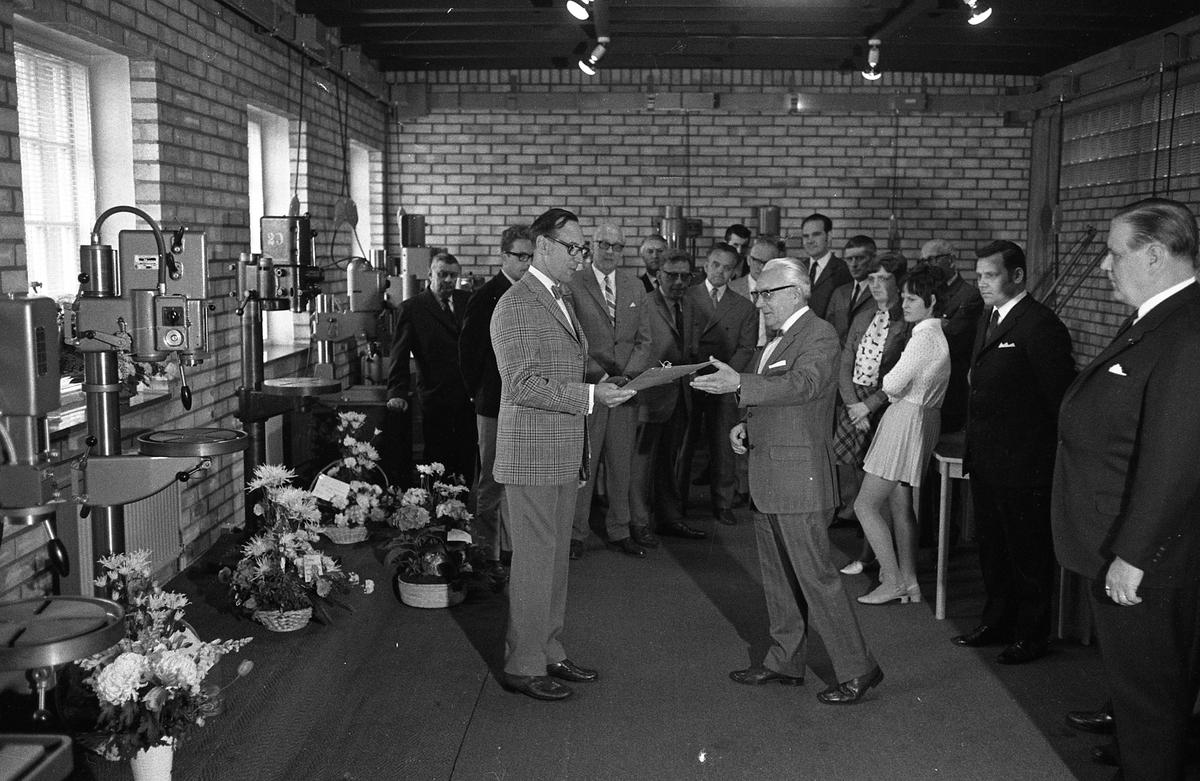 Arboga Maskiner levererar jubileumsmaskin till kund, 1970-talet  En samling kostymklädda herrar och två kvinnor närvarar. Några pelarborrmaskiner står uppställda tillsammans med flera blomsteruppsättningar. Den vänstra mannen, i rutig kavaj, är Hroar de la Cour. Den längste, mörke mannen, mot gaveln, är Göte Wahlfeldt.  AB Arboga Maskiner startade 1934 och tillverkar borr- och slipmaskiner.  Läs om företaget i Reinhold Carlssons bok Arboga objektivt sett.