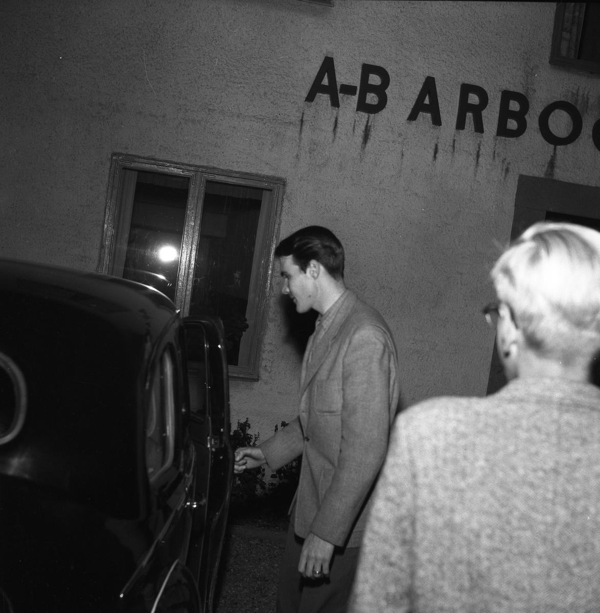 Arboga Maskiner, entré. En man öppnar en bildörr. Mannen är klädd i kavaj och har förlovningsring på fingret.  En annan man står i förgrunden, med ryggen mot kameran. Mannen vid bilen är Göte Wahlfeldt, arbetsstudieingenjör vid AB Arboga Maskiner.  Företaget startade 1934 och tillverkar borr- och slipmaskiner.
