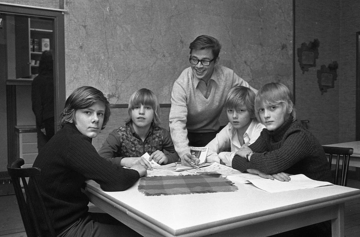 Arboga OrienteringsKlubb. Fyra pojkar sitter vid ett bord. En man visar hur kompassen fungerar. På väggen bakom dem hänger en stor karta. I rummet bredvid finns ett kök.