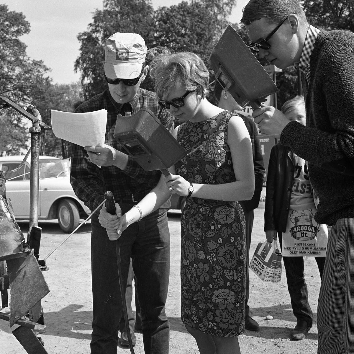 """Arboga Tekniska skola. De äldre eleverna hittar på besvärliga uppgifter åt nykomlingarna. """"Skändning"""" kallas det. Här håller en ny kvinnlig elev på med svetsning medan de andra ser på. En man, iklädd keps från bensinmacken Shell, hjälper henne. En bil syns i bakgrunden."""