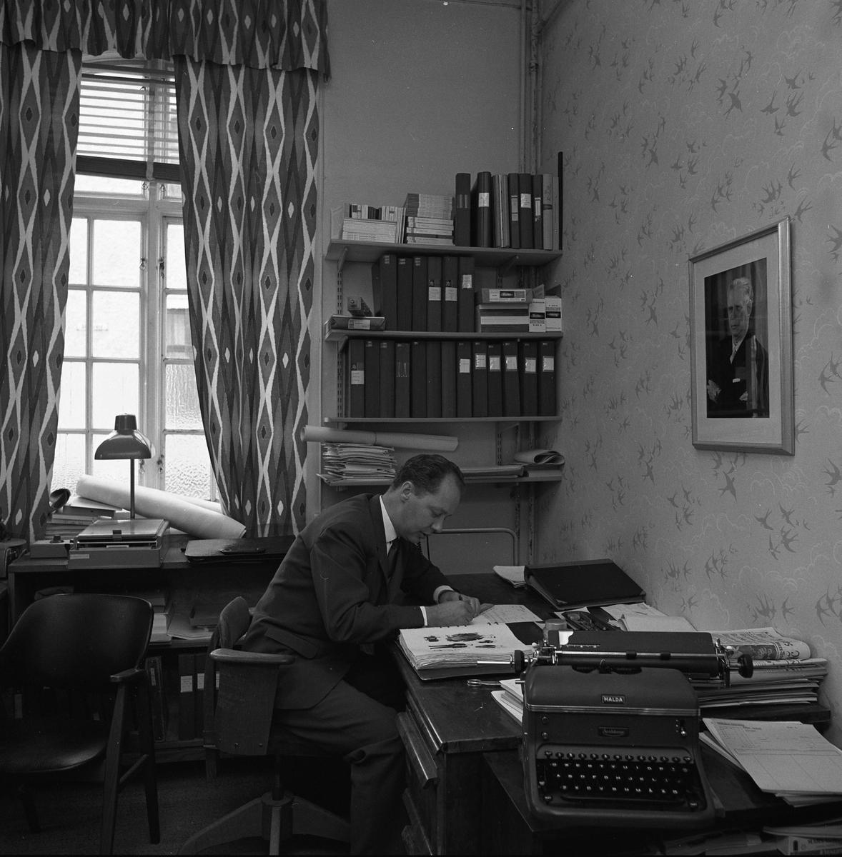 Arboga Tidning, personal och interiör. Willy Johansson, annonschef, sitter vid skrivbordet. Han är klädd i kostym och slips. Vid sidan om Willy finns en väggfast hylla med pärmar. I förgrunden ses en skrivmaskin.