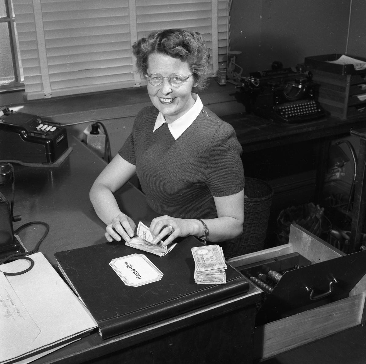 Arboga Tidning, personal och interiör. En kvinna sitter vid skrivbordet och räknar hundralappar. Bredvid henne ligger en bunt tiokronorssedlar. I den utdragna skrivbordslådan syns mynt i rader. På skrivbordet ligger en stor kassabok. Där finns också en telefon och en räknemaskin. På ett bord, bakom henne, står en skrivmaskin. Persiennen är neddragen för fönstret.