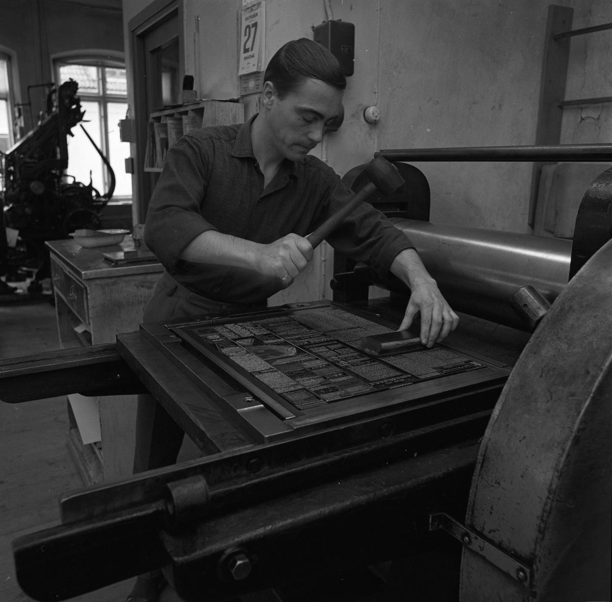 Arboga Tidning, personal och interiör. En man sätter en tidningssida. Han håller en gummiklubba i handen. På väggen hänger en almanacka. En stor maskin skymtar i bakgrunden.