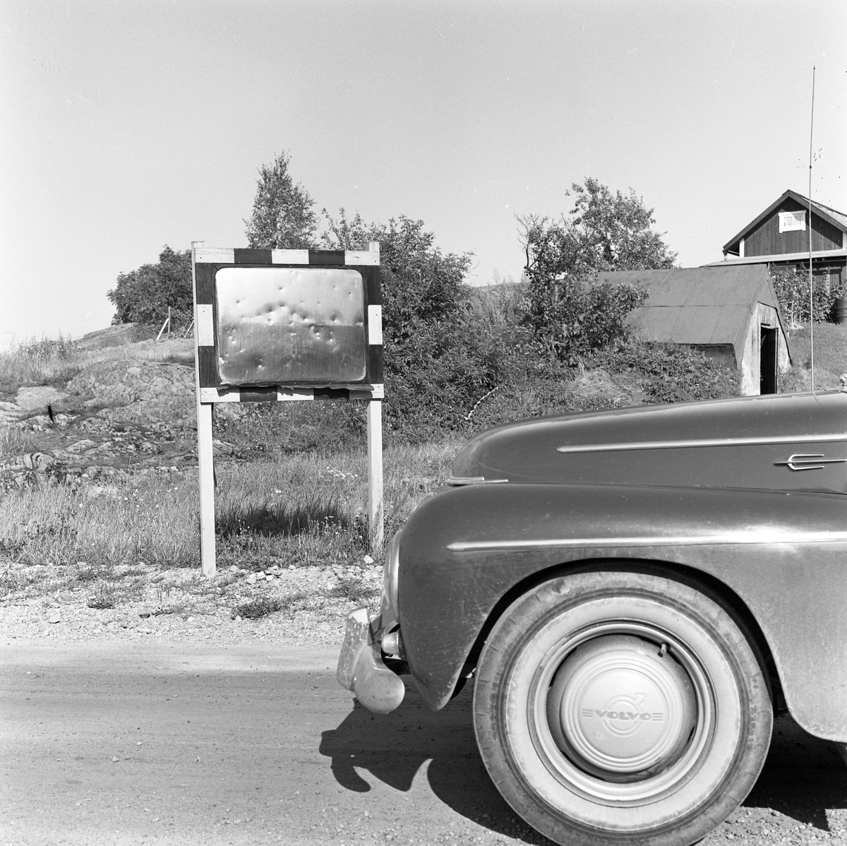 """Motorhuven på en bil. Bilen färdas på en grusväg. En övervakningsspegel / """"skvallerspegel"""" är uppsatt i vägrenen. Bortanför bilen ses två byggnader i en backe. Det ena huset är ett boningshus."""