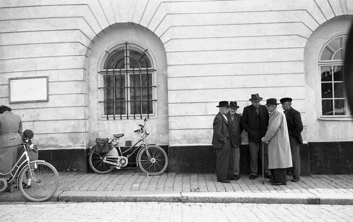 Fem äldre män har träffats på gatan. Fyra bär hatt och en bär keps. En man har käpp.  Byggnaden inhyser polisstationen och ett av fönstren är försett med järngaller. Under fönstret står en cykel med packväskor. Till vänster i bild skymtar en kvinna, ett barn och en cykel.