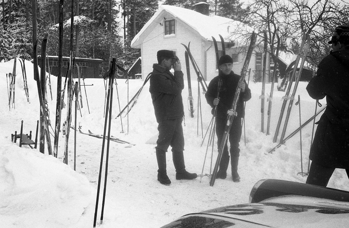 """Skidtävlingen AT-loppet. Lennart """"Svarten"""" Pettersson fotograferar Torsten Eriksson med skidor. Båda männen är från Medåker. Längdskidor och stavar står nedstuckna i snön. I förgrunden syns motorhuven på en bild. (AT kan betyda Arboga Tidning)."""