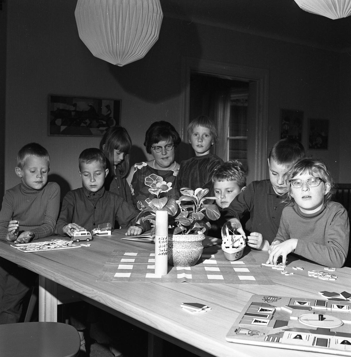 Barndaghemmet. Sju barn och fröken Astrid Eriksson, sitter vid ett bord. Där finns pussel och barnen leker med bilar och båtar.