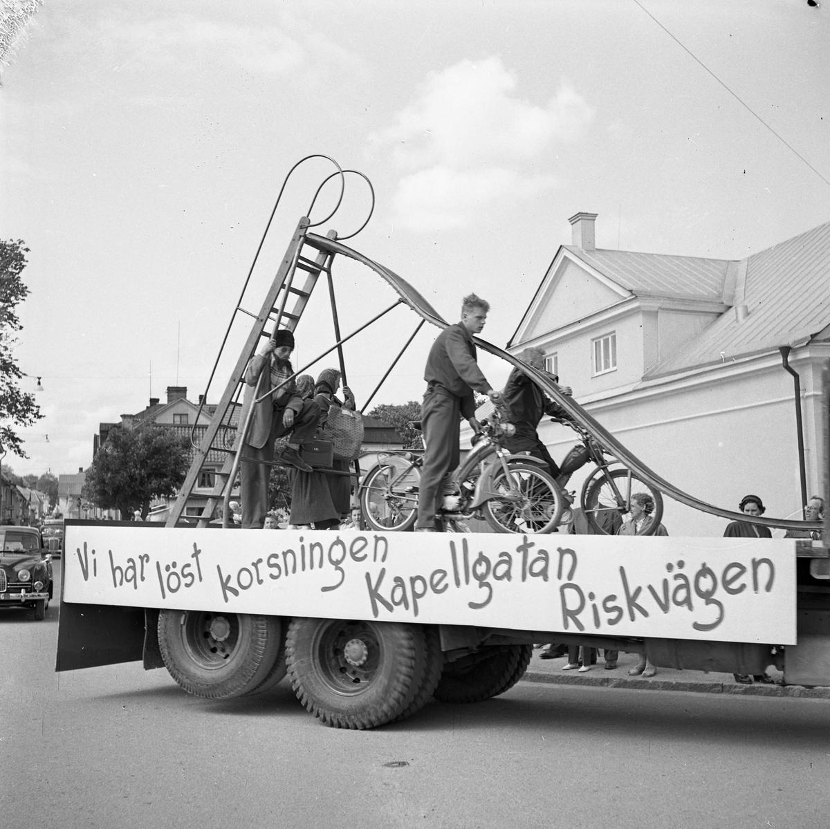 """Barnens Dag firas. En lastbil med texten """"Vi har löst korsningen Kapellgatan Riskvägen"""" och en rutschkana på flaket. Där står även två grabbar med var sin moped."""