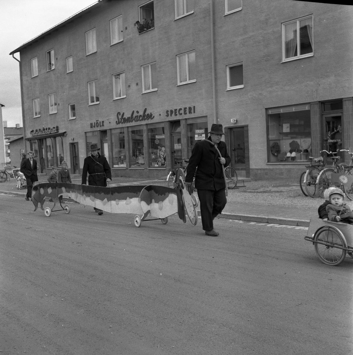 Barnens Dag firas. Två män leder en flera meter lång Bassethund på hjul. Framför dem ses en liten pojke i en kärra. Han har en Barnens-Dags-flagga i handen. I bakgrunden ses Stenbäcker Mjölk och Specerier.