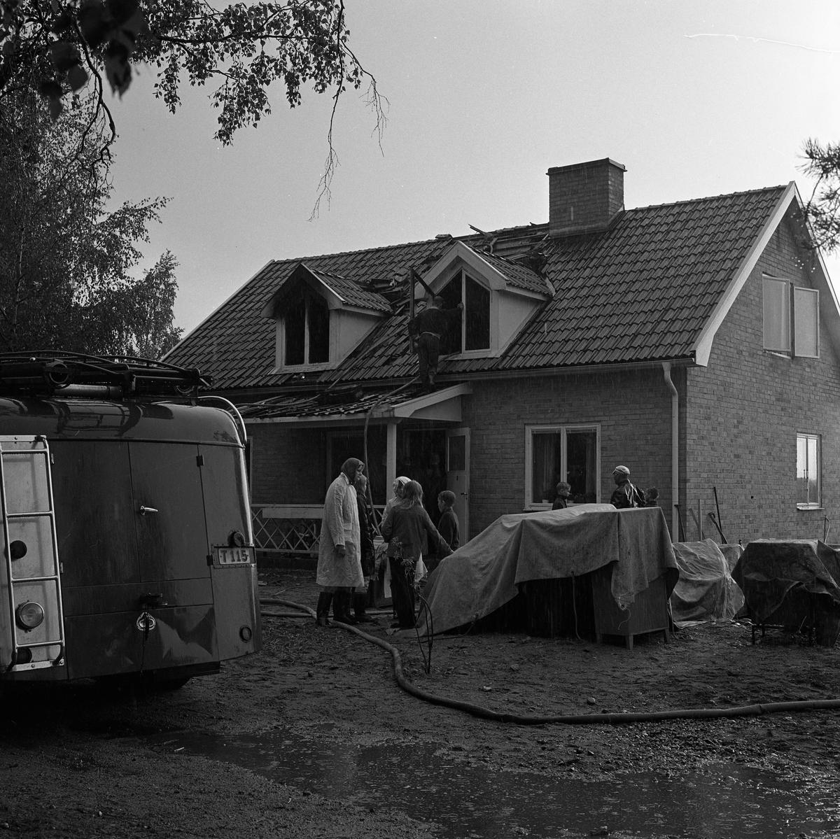 Det har brunnit i en villa i Lunger. Brandkårens bil, med vattenslang, är på plats. Människor är samlade utanför huset.