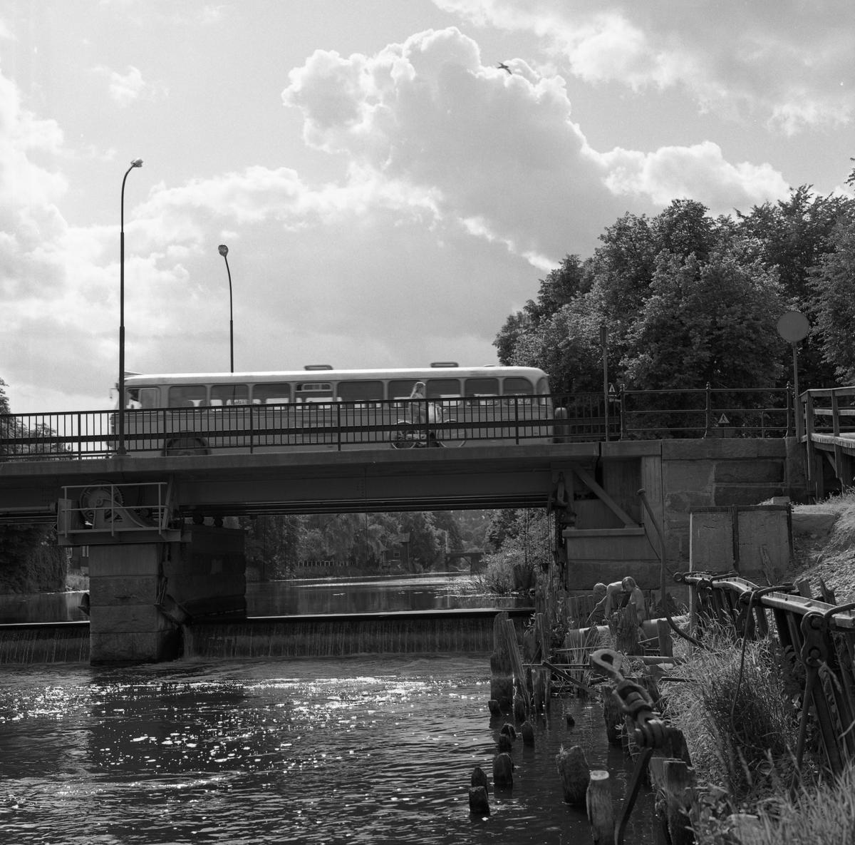 En buss kör över Herrgårdsbron. En flicka cyklar. Två pojkar sitter vid norra brofästet. Under Herrgårdsbron syns Kapellbron. Arbogaån på sommaren.