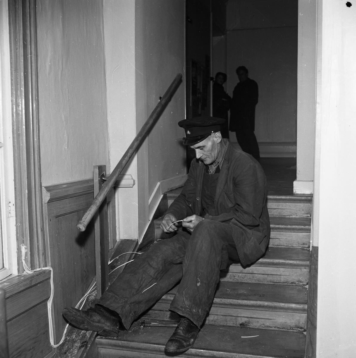 Reparationsarbete efter branden i televerkets lokal på Nygatan. En man sitter i en trappa och lagar ledningar. Han har arbetskläder och en keps med Televerkets märke på.