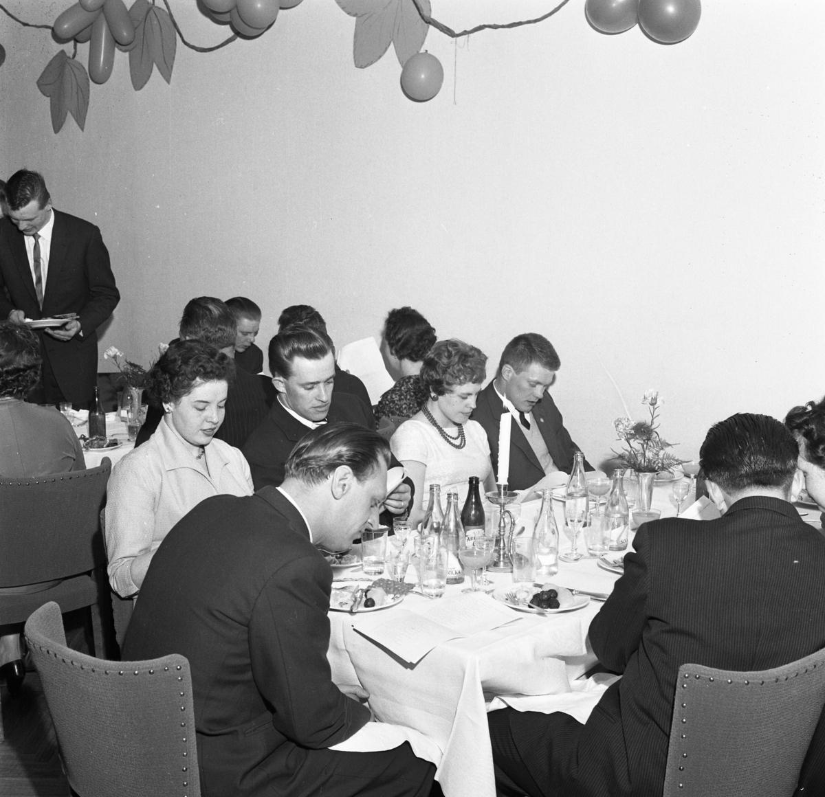 Elektrikerförbundets Arbogaavdelning firar jubileum. Uppklädda  män och kvinnor vid borden. Köttbullar och potatis på tallrikarna. Dekorationer på väggen.