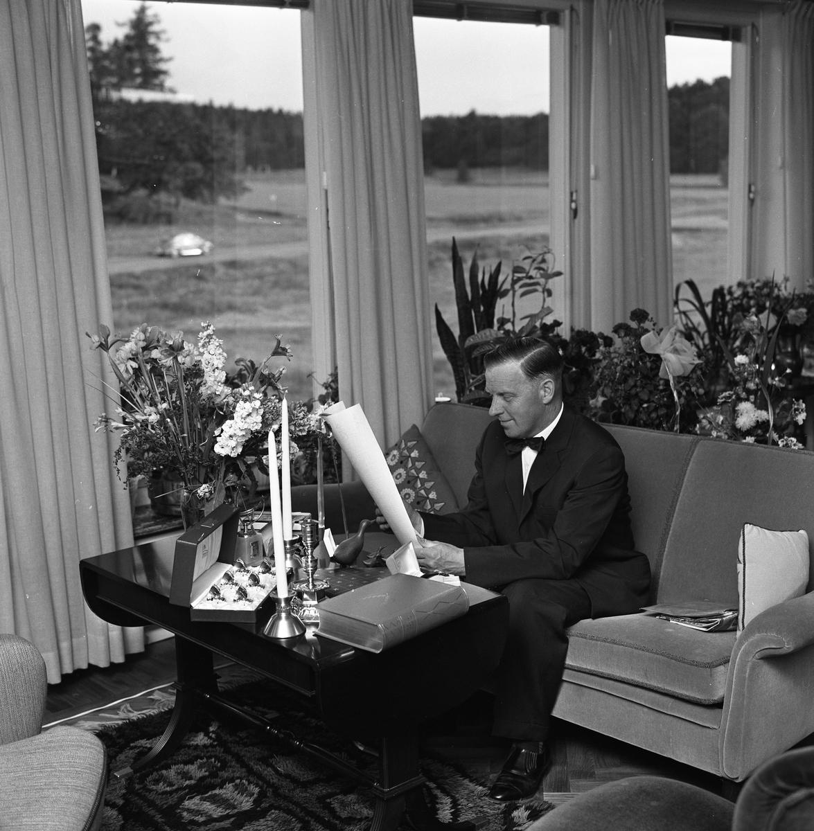 Erik Holm (kallad Glass-Holm), sitter i sitt vardagsrum och tittar på sina 50-årspresenter. Han har bland annat fått ljusstakar och många blommor. Möblemanget består av soffa, två fåtöljer, ett bord och en ryamatta. Stora fönster vetter mot landskapet utanför.