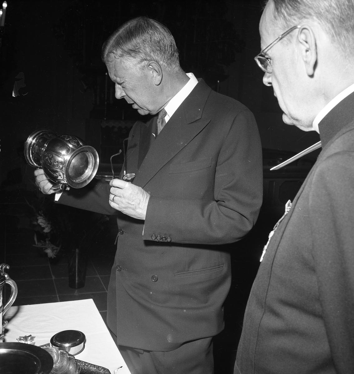 Konung Gustaf Vl Adolf är på Eriksgata. Här får han titta på silversamlingen i Heliga Trefaldighetskyrkan tillsammans med prosten E Olof Björsell. För värdskapet, under kungens besök, svarade stadsfullmäktiges ordförande Jonas Carlsson och kommunalborgmästare Danliel Ekelund. Den organisationskommitté som ansvarade för arrangemangen, hade hos drätselkammaren begärt en summa av 3000 kronor för att täcka kostnaderna vid kungabesöket. Beloppet beviljades.  Tiden för kungens besök var beräknad till 130 minuter.
