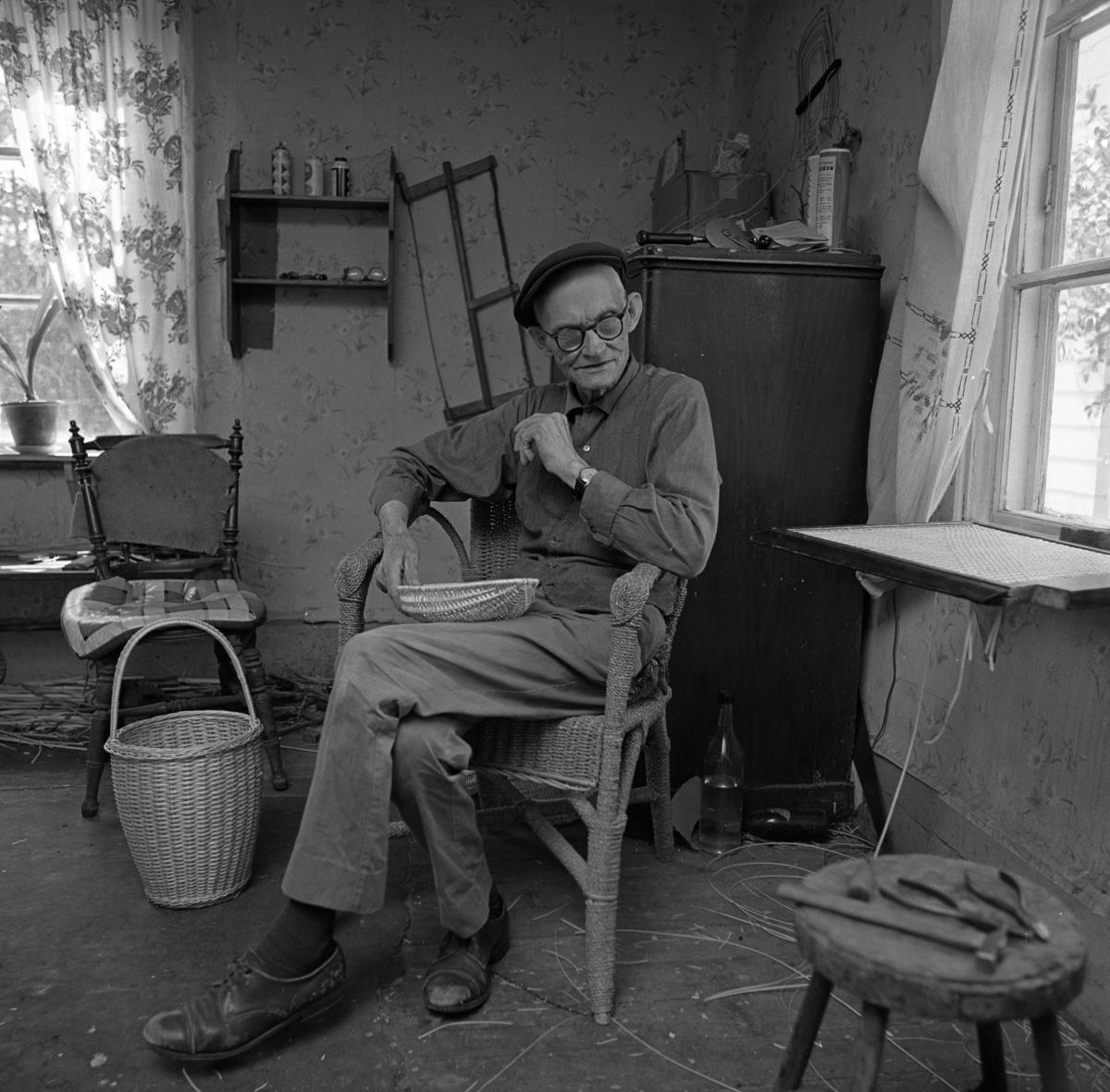 Korgmakare Oskar Larsson i Sjölunda, Tyringe. Oskar har sin verkstad i ett av rummen i bostadshuset. På väggen hänger en såg. En färdig korg står på golvet. På byrån ligger en borr. På pallen ligger ett par tänger och en hammare. Det står krukväxter i fönstret. Oskar är gift med Maja. Oskar lärde grannbarnen att spela schack.