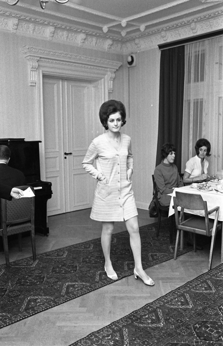 En randig klänning med knäppning och fickor visas på TBV´s modevisning. Modellen heter Ylva Martinsson. Vid bordet sitter Ingrid Östling och Anne-Marie Andersson och dricker kaffe och äter landgång. En man spelar piano. Eftersom Sture Melander ses på en bild i sammanhanget, kan man gissa att kläderna kommer från Öhrman & Melander.