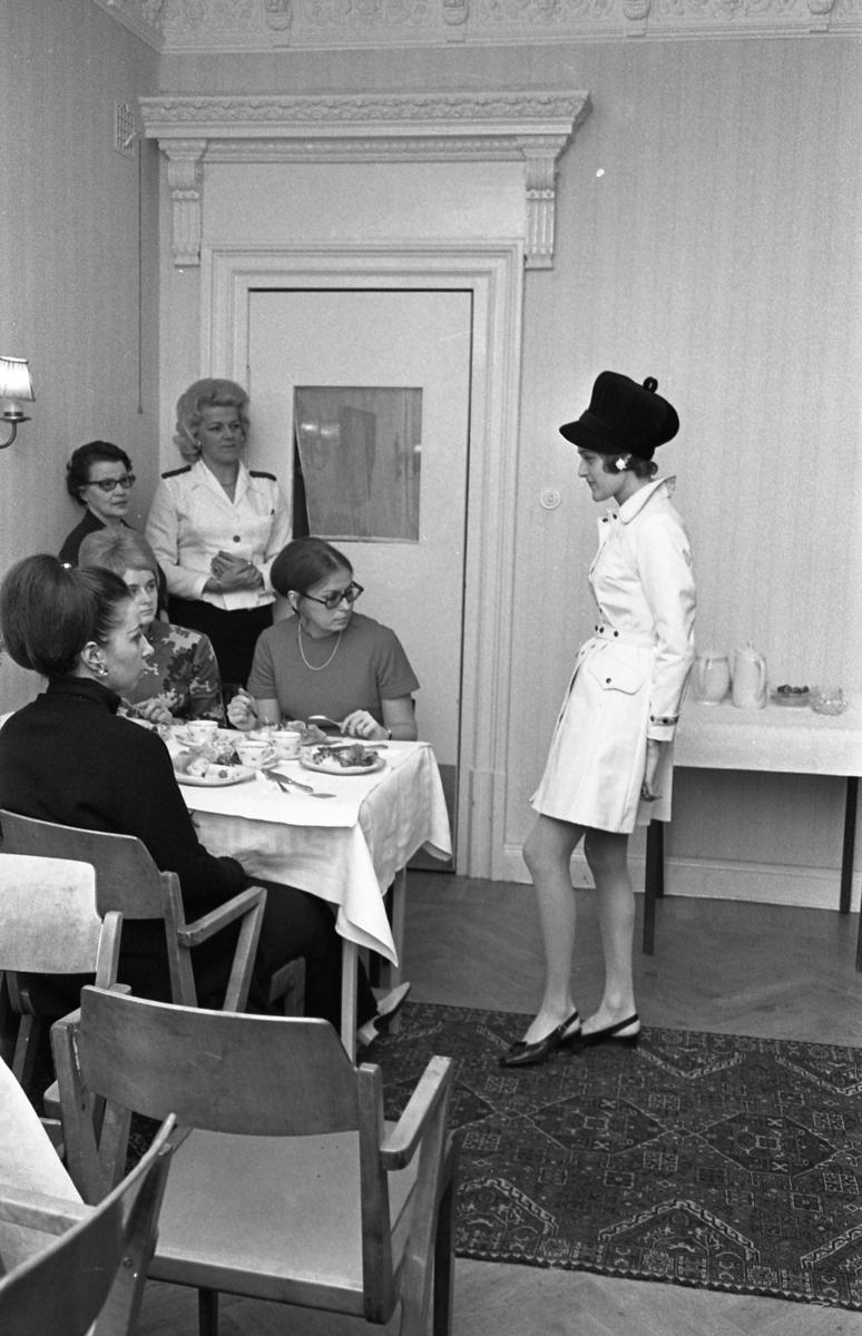 TBV ordnar modevisning och bjuder på kaffe och landgång. Aino Lindqvist är servitrisen vid dörren. Vid bordet sitter Ann-Marie Törnqvist (blond) och Gunilla Hammarlund (mörk med glasögon). Mannekängen, som visar trenchcoat och keps, heter Gunilla Magnusson. Eftersom Sture Melander ses på en bild i sammanhanget, kan man gissa att kläderna kommer från Öhrman & Melander.