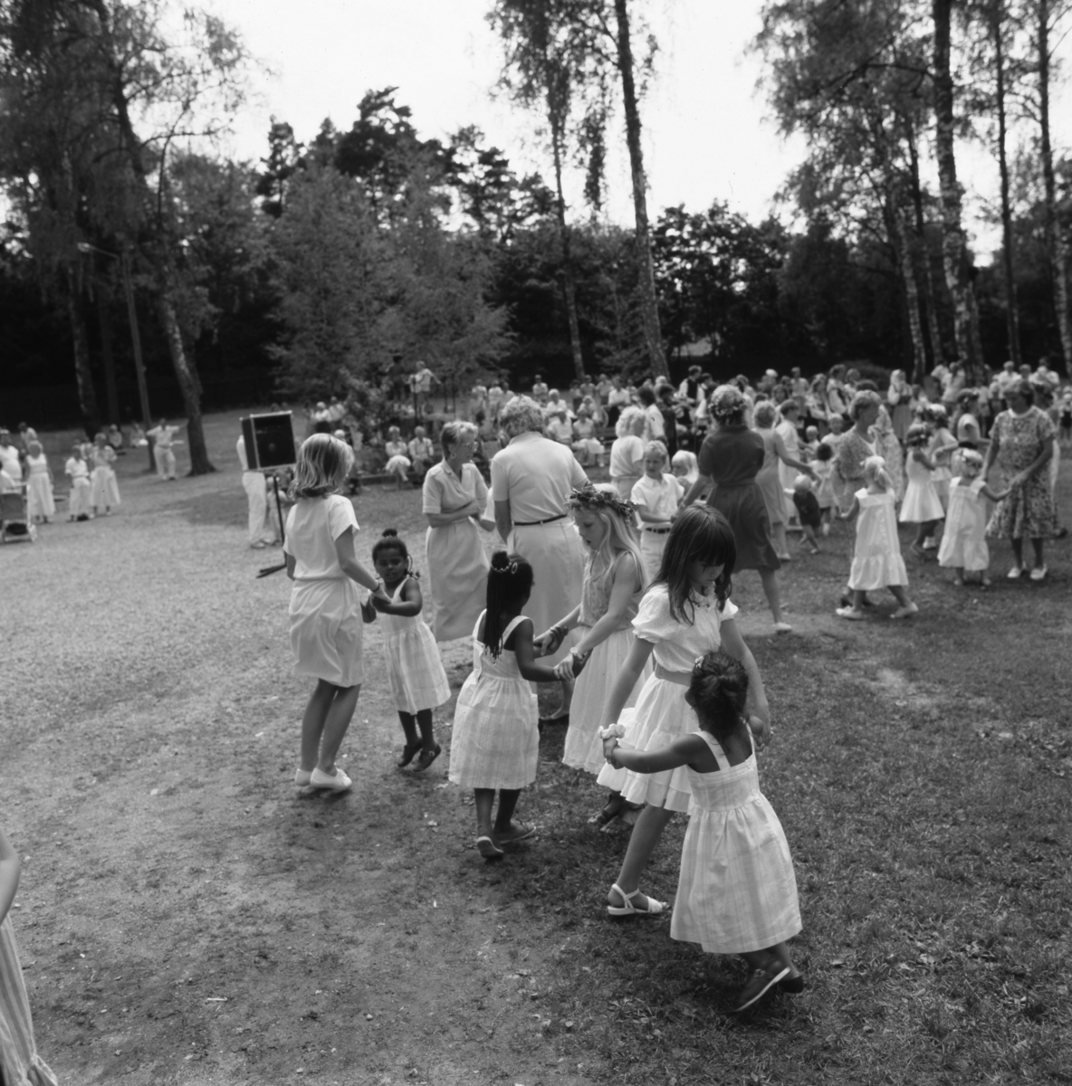 Det är midsommarfirande i Folkets park. Kvinnor och barn dansar ringlekar. Många har finklänningen på sig och en del har blomsterkransar i håret. På ett stativ står en högtalare.