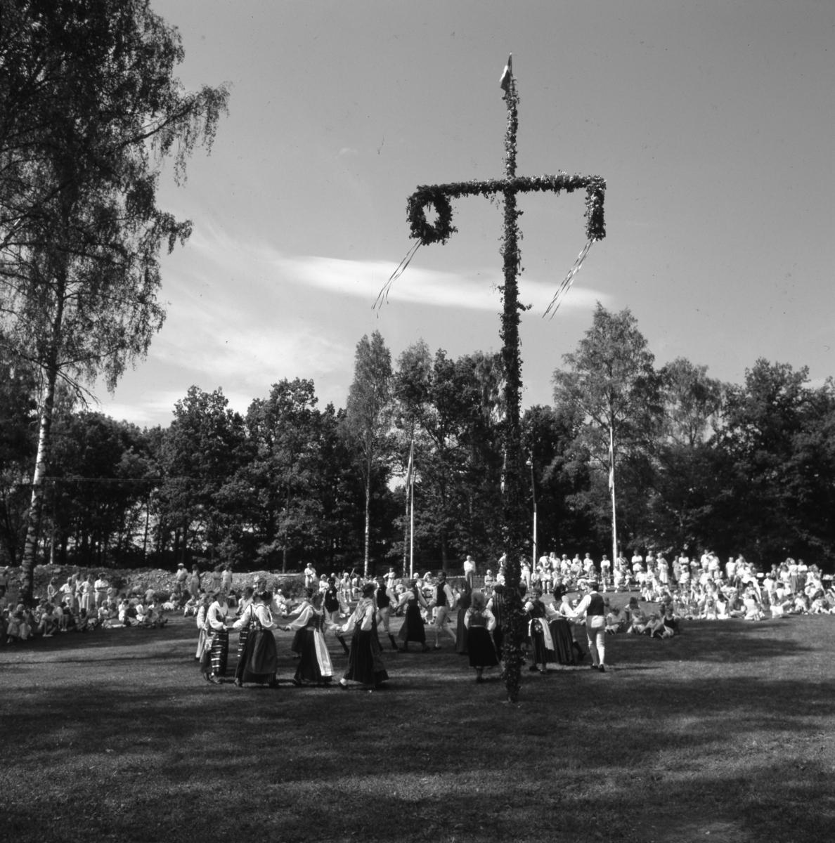 Midsommarfirande i Folkets park. Midsommarstången är rest och flaggorna hissade. Folkdanslaget uppträder på gräset. Publiken sitter utspridd.