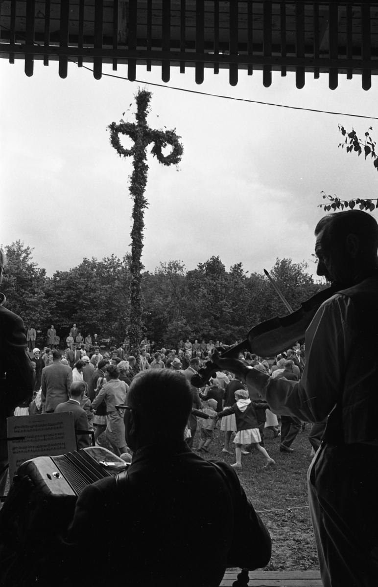 Midsommarfirande vid Godtemplarnas sommarplats. Män, kvinnor och barn dansar runt midsommarstången. De har ytterkläder på sig. Spelmännen, en med dragspel och en med fiol, är på en scen under tak.
