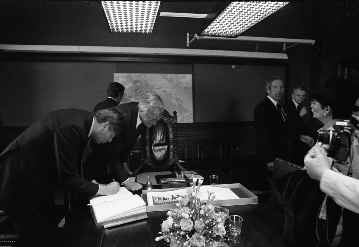 Riksdagspolitiker befinner sig i Arboga för att delta i firandet av Sveriges riksdags 550-årsjubileum. Lennart Bodström skriver (i gästboken?). Bilden är tagen på rådhuset. Är den leende mannen, med glasögon, möjligen Ove Reiner? En snidad karmstol står vid bordsänden. En vacker blomsteruppsats står på bordet. På väggen hänger en karta. Till höger ses Arbogas kommunalråd, Per-Olov Nilsson. Kvinnan närmast kameran är Anita Gradin. Riksdagsjubileet 1985.