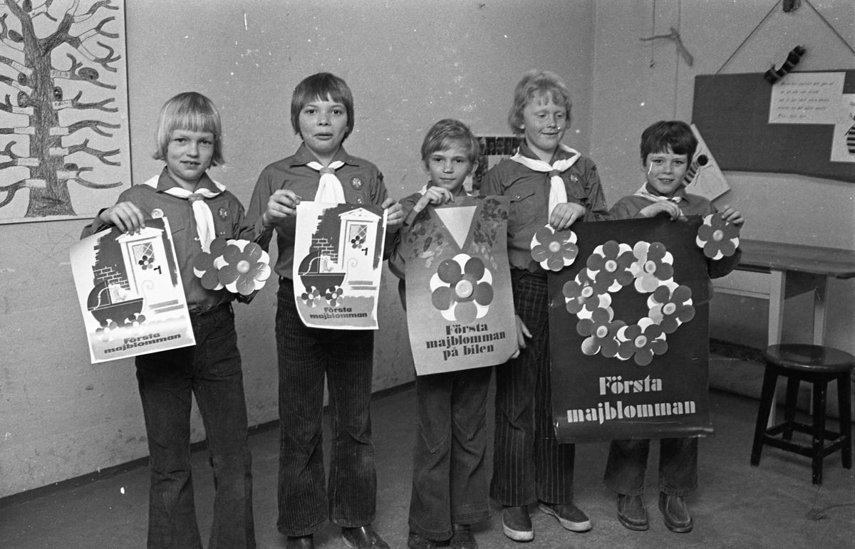 Scouter säljer majblommor. De har sina scoutskjortor och sjalar på sig och håller i affischer och klistermärken. Den fjärde scouten från vänster är Jens Gunnarsson.