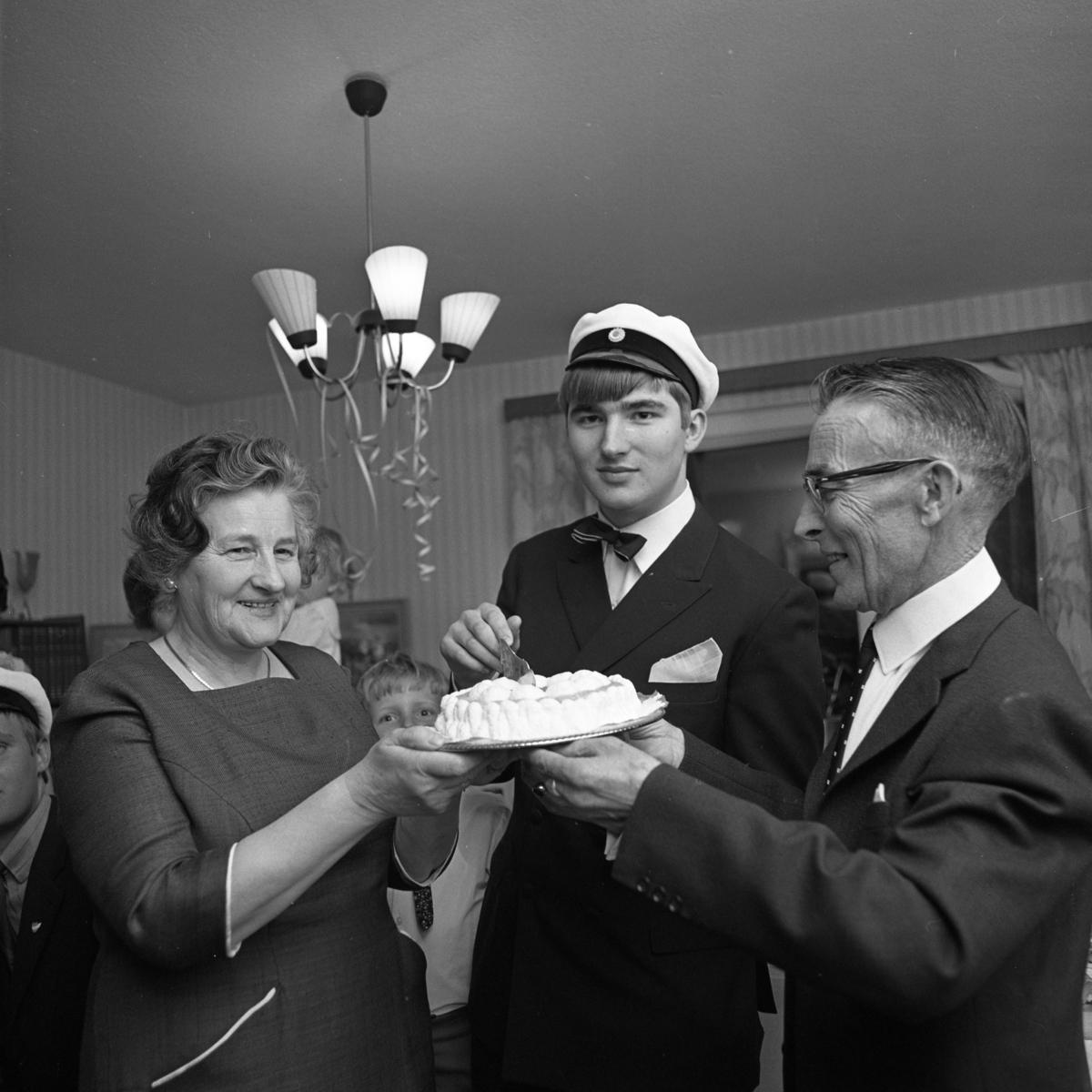 """Lars-Göran Rådström har klarat studentexamen (han ingick i den sista """"kullen"""" som hade muntliga förhör). Mamma Karin och pappa Egon håller i tårtan."""