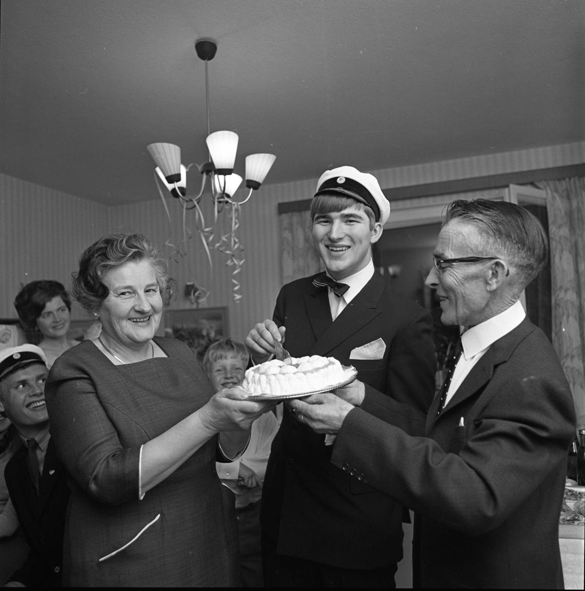 Lars-Göran Rådström har klarat studentexamen. (Han ingick i den sista kullen som hade muntliga förhör). Mamma Karin och pappa Egon håller i tårtan. I bakgrunden ses studentkamraten Hans Grönkvist, Lars-Görans storasyster Mona-Lisa Bergström och hennes son Tomas Bergström.