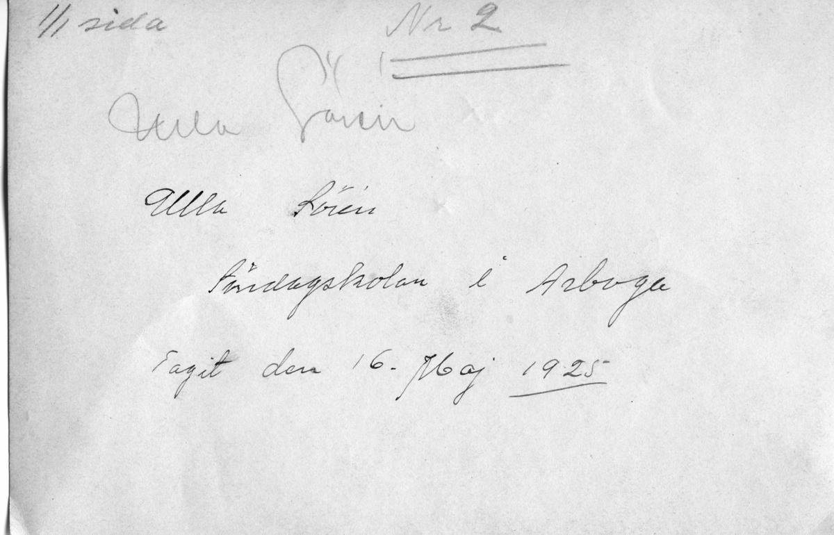 Baksidestext på ett fotografi föreställande barn i söndagsskolan. Framsidan ses: AKF-12063  Namnet Ulla Sörén är skrivet på bildens baksida. Bilden är tagen den 16 maj 1925.