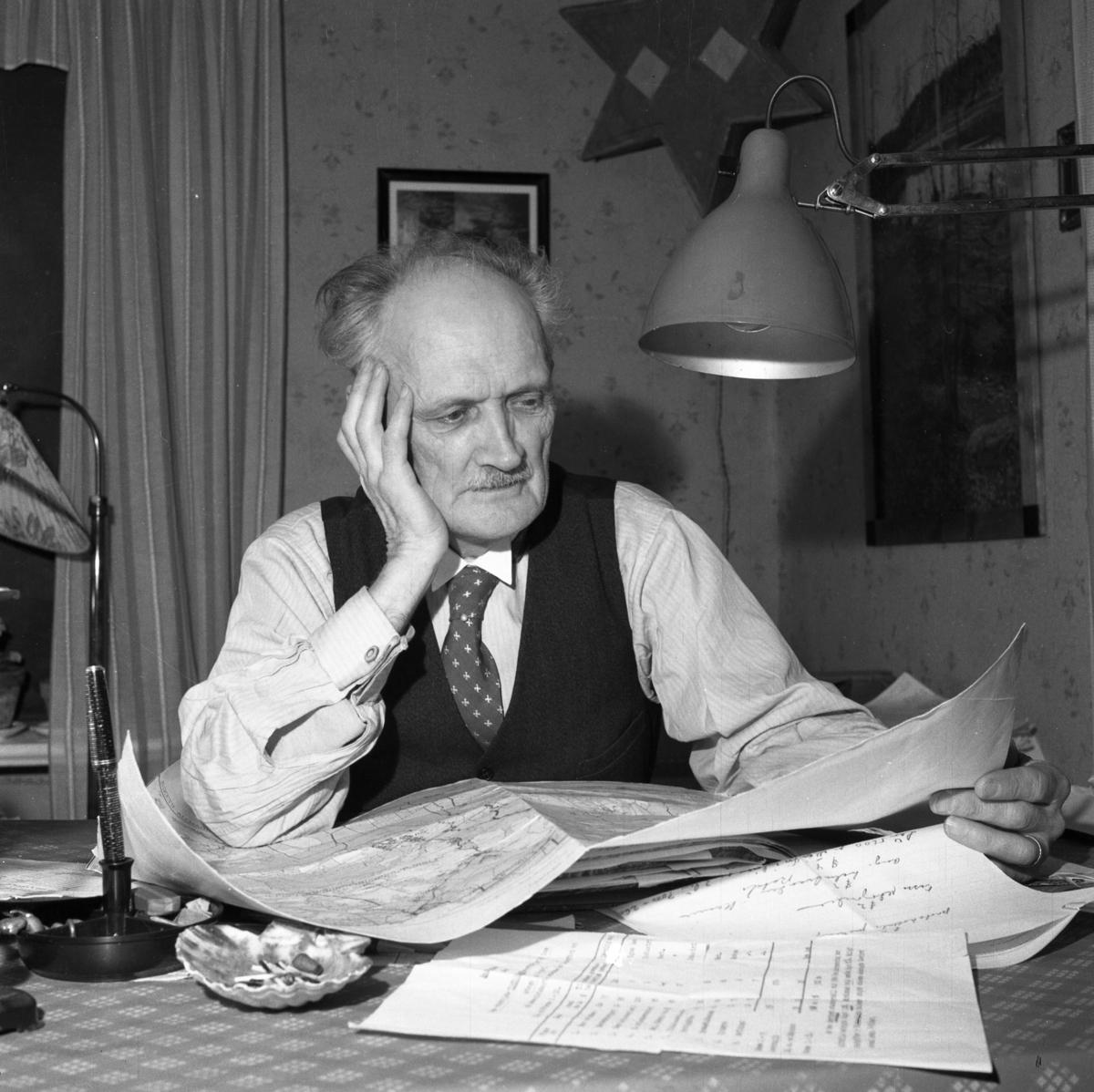 En man sitter vid bordet och ser på en karta. Fler papper ligger på bordet. Han har en lampa på väggen och en på bordet. Bakom honom ses två tavlor. Bilden användes till en artikel, i Arboga Tidning, om kommunsammanläggningen.