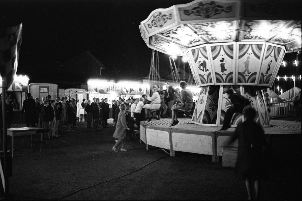 Ungdomar på nöjesfältet på Hamntorget. Några åker karusell med slänggungor.