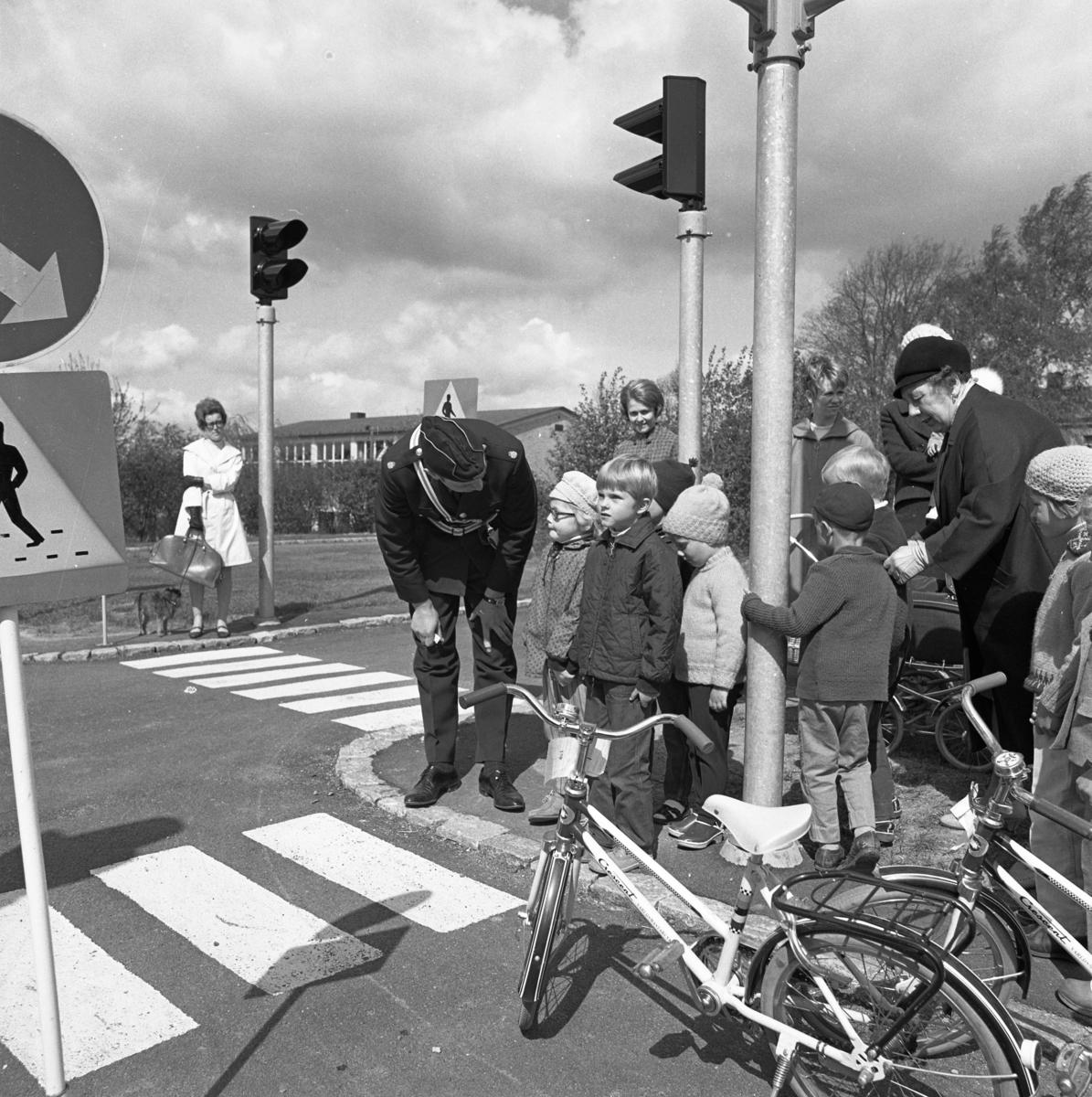 Trafiklekskola med polisman Leif Ekström, i uniform. Barnen får lära sig om trafikregler, trafikskyltar, övergångsställen och trafikljus. Några mammor är också med. I bakgrunden står en kvinna med en hund. Gäddgårdsskolan skymtar. Bilden är tagen nära Borgmästargatan.