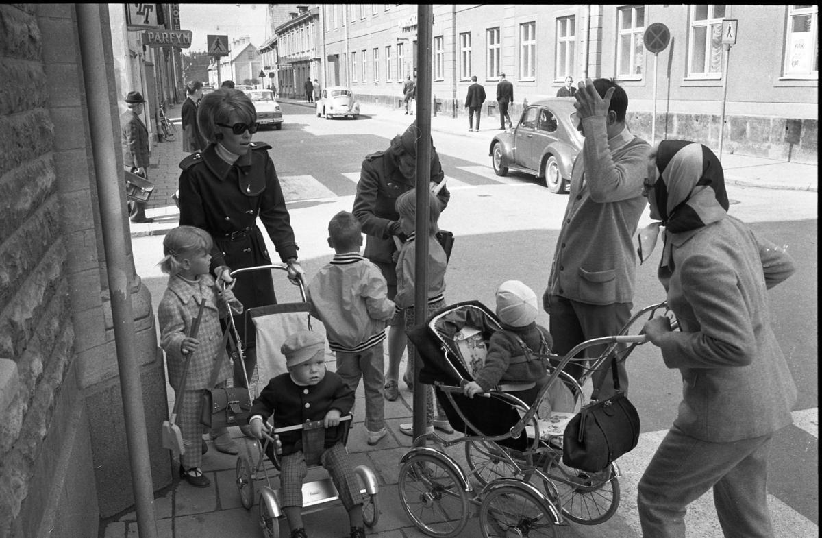 Trafikpropaganda. Bilkårist Britt-Marie Utterström i kontakt med människor på trottoaren. Mannen, till höger, är Göran Widin. På vänster sida av Nygatan ligger VLT´s lokalkontor, parfymeriet och hotellet. På höger sida, framför Folkvagnen, ligger Systembolaget.
