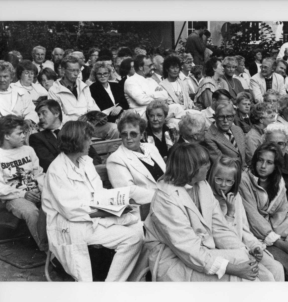 """Publiken samlad för att se föreställningen """"Giv oss fred"""" på museets innegård. På andra raden nerifrån, tvåa från vänster, sitter Birgit Johansson. """"Giv oss fred"""", även kallat """"Arbogaspelet"""", är ett teaterstycke skrivet av Rune Lindström 1961. Handlingen, som är inspirerad av Arbogas klosterhistoria, är förlagt till början av 1500-talet. Uruppförandet skedde den 11 augusti 1962 och Rune Lindström spelade Engelbrekt Gertsson. Lions Club i Arboga stod för arrangemanget. Föreställningarna regnade bort och det blev ett stort ekonomiskt bakslag för föreningen. Spelet har framförts igen; 1987, 1988, 2012 och 2015 av medlemmar i """"Bygdespelets Vänner""""."""