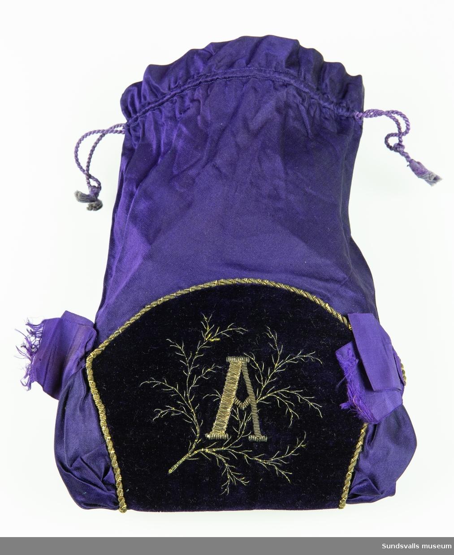 Redikyl i mörkt lila siden med infällning av sammet i samma färg. Ripsbandsrosetter på båda sidor. 'A' är broderat med guldtråd på sammetspartiet. Dragsko med snörmakeriband.