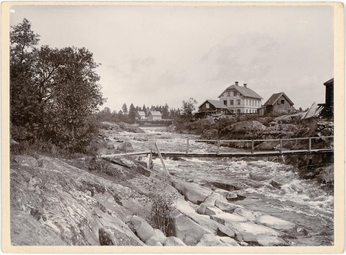 Gångbro över fors, bostadshus i bakgrunden, Högsby, Småland