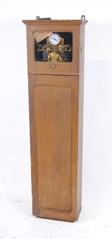 """Tågkontrollur, elektriskt, med skrivare av Siemens & Halske fabrikat. På urtavlan står det """"Siemens & Halske Berlin."""" samt stämplat """"SIEMENS & HALSKE BERLIN No 68215"""" i mässing på urverket. Uret har ett klockfodral av trä som ett golvur och är ådringsmålat i brunt. Upptill, framför urtavlan och skrivaren, sitter en limmad pappersremsa med tryckt text på tyska, samt en likadan på väggen bakom urverket. Texten på remsan: """"Diese Uhr darf nie durch Drehung der Zeiger richtig gestellt, sondern es muss dies stets durch Drehung der Papiertrommel be wirkt werden"""". Uret har fyra ingångar för ström döpta """"L2"""", """"B"""", """"E"""" och """"L1"""". I botten av uret ligger ett paket inslaget i papper. Den nedre luckan är låst och nyckel saknas. Nyckel för uppdragning av ur sitter fast med en ståltråd i ett av beslagen upptill. På baksidan av uret finns två utgångar för elektriska sladdar. På framsidan av luckan, över glaset, är det skrivet med blyertspenna """"Tillhör (överstruket Säiö?) G station...(oläsligt)""""."""