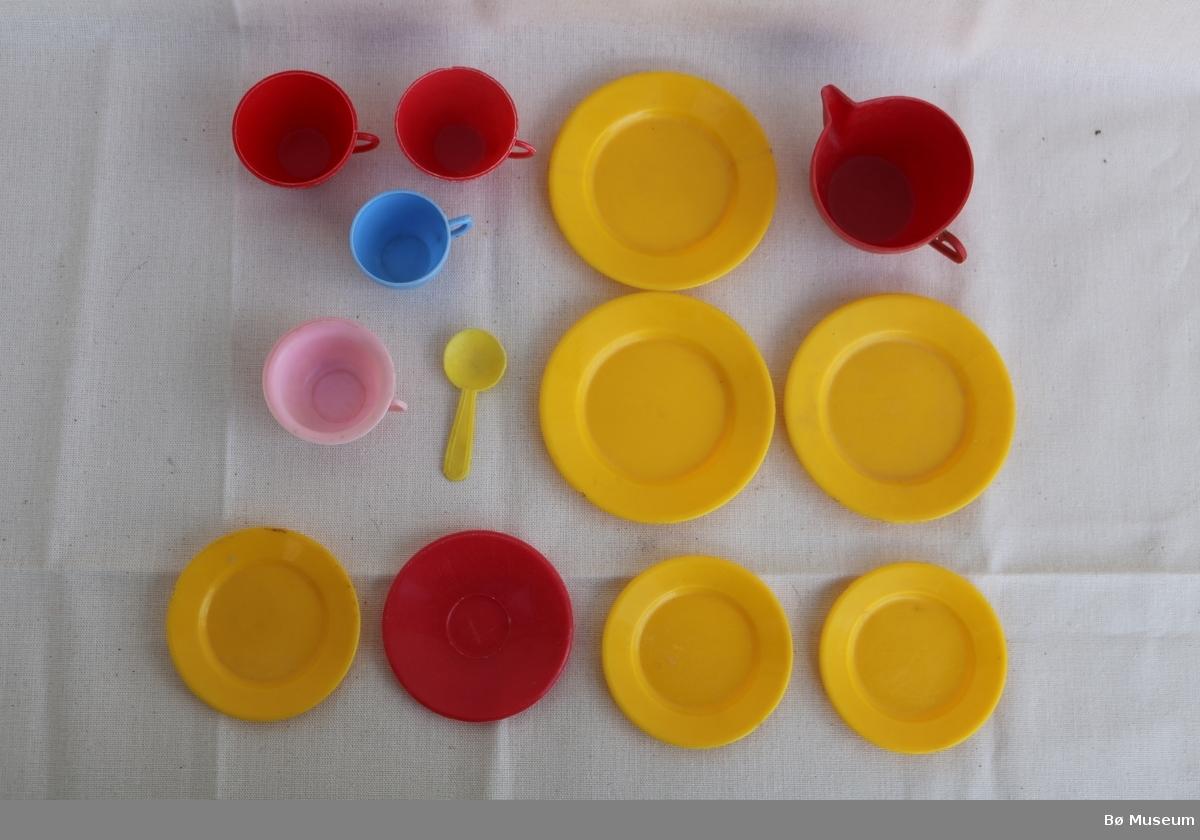 Leikeservise i plast, pluss 1 plastskjei.  a - gul asjett, 3 stk. b - gul tallerken, 3 stk. c - raud kaffiskål, 1 stk. d - raud kaffikopp, 2 stk. e - raud fløytemugge, 1 stk. f - rosa kaffikopp, 1 stk. Kunne eventuelt ha vore ei gamaldags tissepotte som ein har under senga. g - blå kaffikopp, 1 stk. h - gul skjei