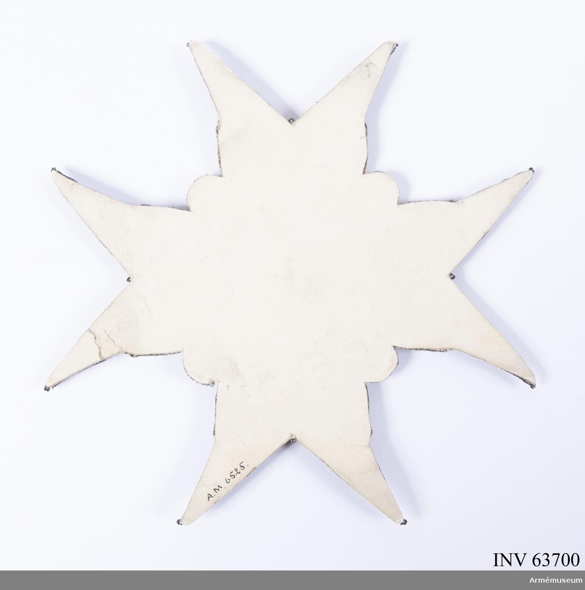 Grupp M II.   Ett St Georgekors av silverbrokad med djupt kluvna armar och mellan dem bevingade änglahuvuden.   I mitten en paljettkrans omgivande en gul glob av vattrat siden är broderat IHS (med ett kors ovanför H:et), samt Sveriges tre kronor.  Nedanför den nedersta kronan tre rosor på stjälkar.