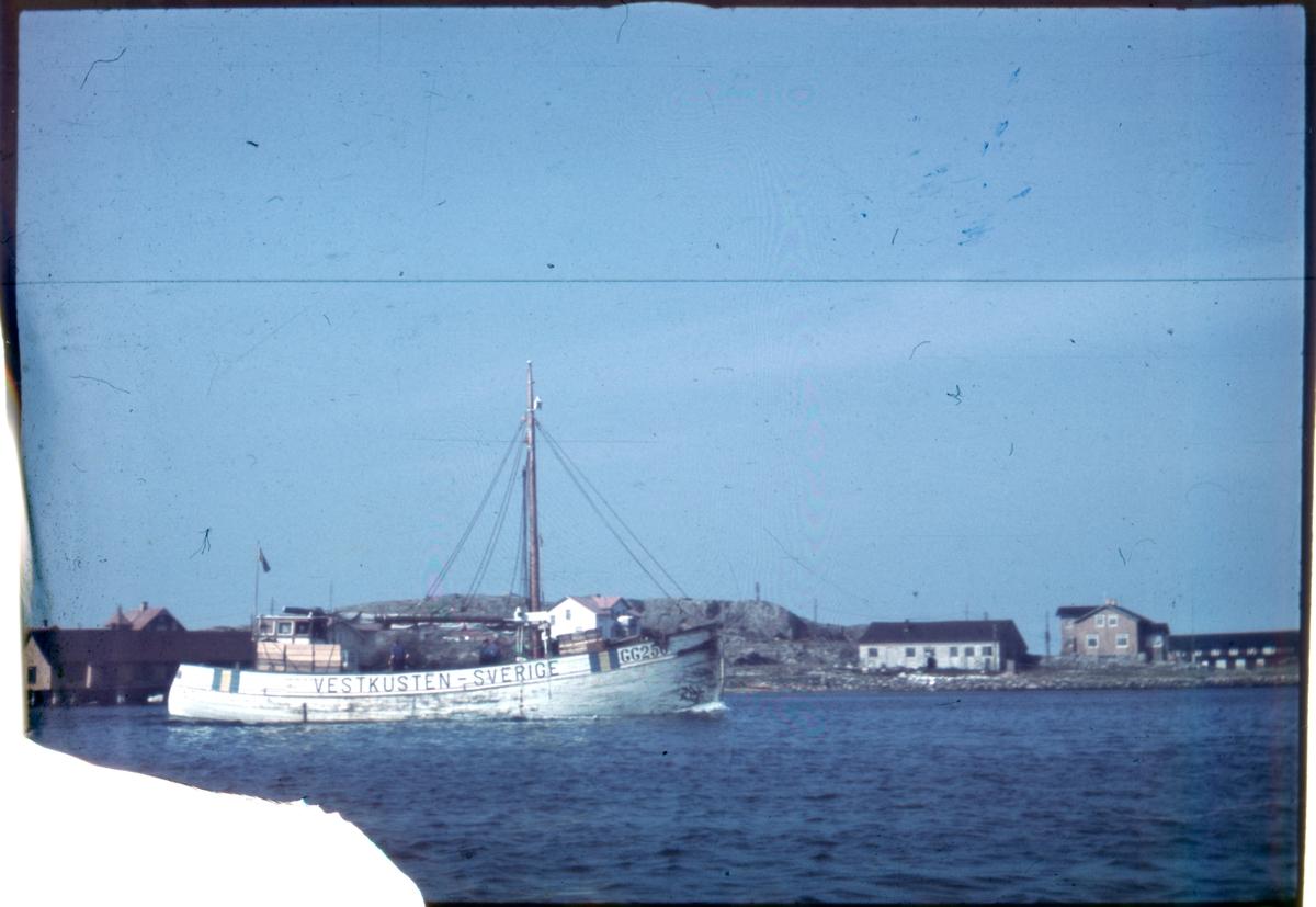"""Enligt noteringar: 70 st. ramade dia. + 5 st. burkar med oramade dia. Båtar, Varv, Hav, Människor.  Film nr. 129  På väg ut ur hamnen GG 250 """"Vastkusten"""" (beskuten och sänkt av tyskarna 25 aug. 1943 i Nordsjön alla man borta, skepparen Torsten Alexandersson ej på bild) Björnhuvudet till höger med Ivar Jonssons smedja, det låga vita huset."""